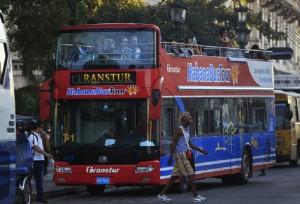 Turistas extranjeros observan el paisaje urbano desde un bus turístico en una céntrica calle de La Habana, en Cuba. Crédito: Jorge Luis Baños/IPS