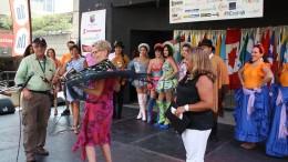 La Premier Kathleen Wynne modela un chal bordado a mano en España que le fue regalado por Fernando Valladares (izquierda), director de Hispanic Fiesta, durante su visita a la comunidad hispana el sábado por la tarde. A la derecha, observa la MP Cristina Martins.